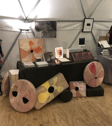 The Dispersed Holdings booth, with pillows by Merritt Meachem, via Art Observed